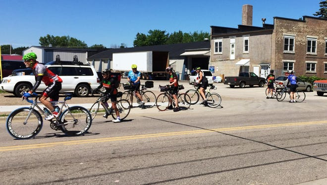 Bikers pass by the Stevens Point Brewery on Tuesday