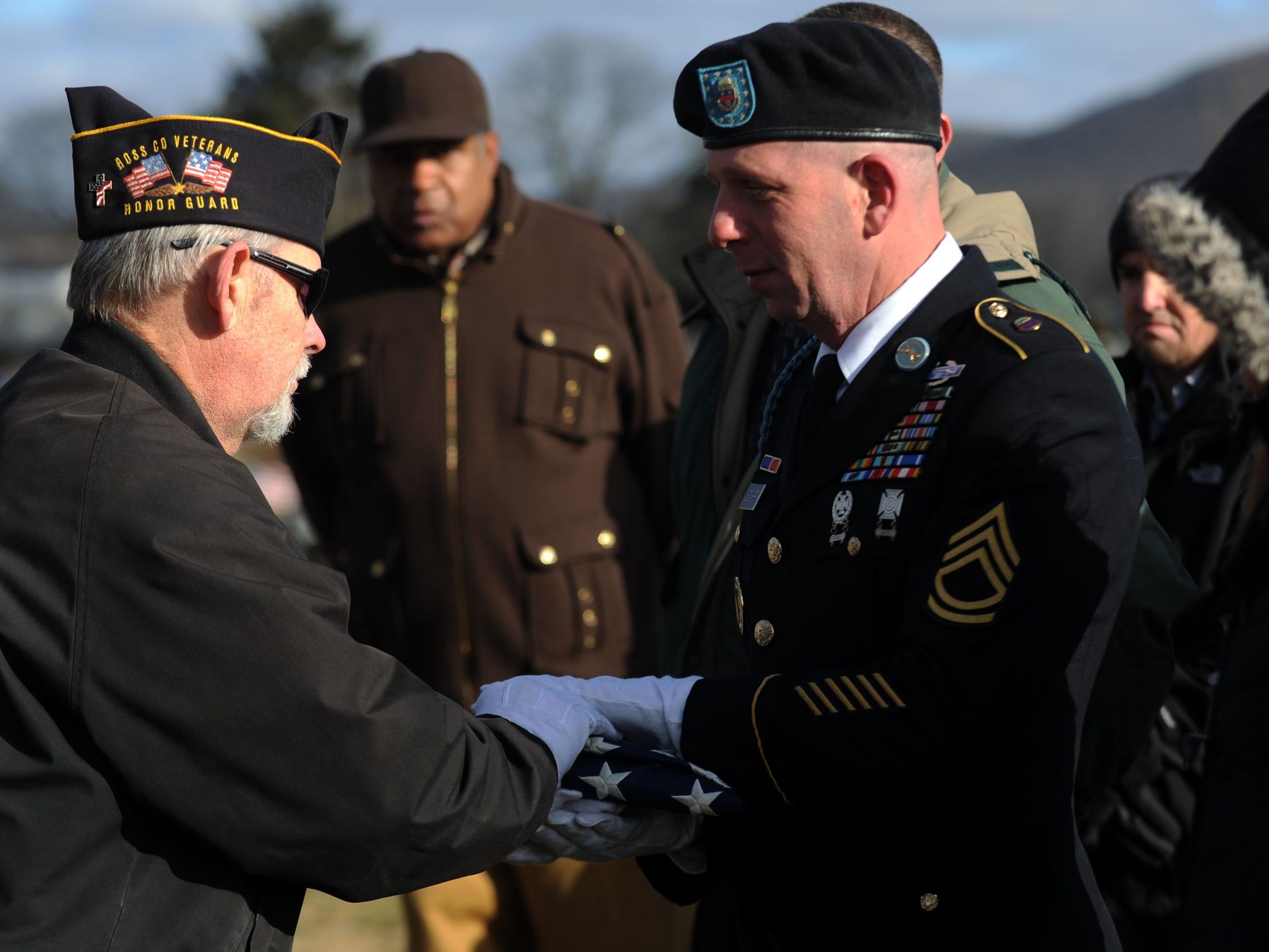 Ira Ayers, left, hands a folded American flag to Jason