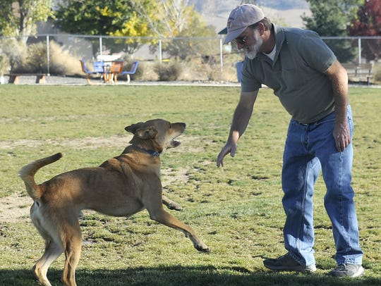 Bob Yesenskiy plays with one of his dogs at the Dayton