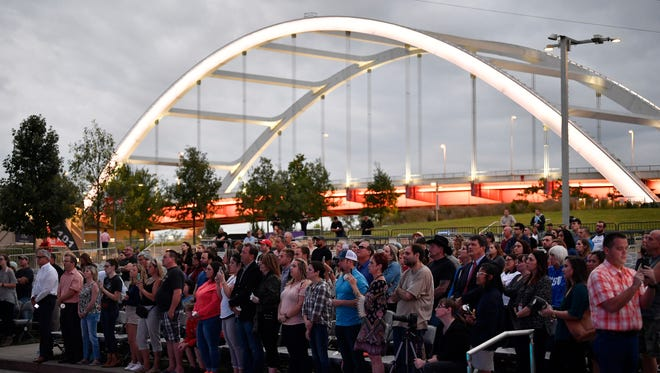 The crowd stands with the Korean Veterans Bridge as a backdrop at Nashville's vigil for Las Vegas shooting victims Monday, Oct. 2, 2017, at Ascend Amphitheater in Nashville, Tenn.