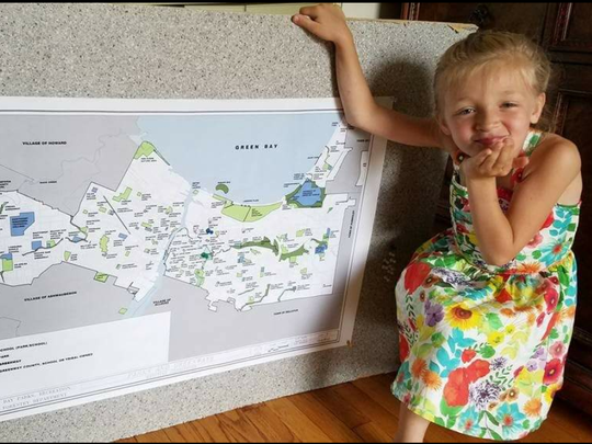 Lily Moore, 7, poses with a map Green Bay Parks, Recreation and Forestry Director Dawne Cramer gave her to track her progress on visiting all of the city's parks.
