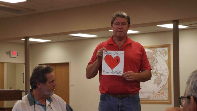 John Rosenberg, center, a volunteer with Kairos Prison Ministry of New Mexico, presents a picture of a heart, drawn by the residents at Southern New Mexico Correctional Facility, near Las Cruces, to show their gratitude during the Autumn 2015 Kairos Weekend at the facility.  Kimble Kearns, Kairos Weekend leader, sits at the far left.