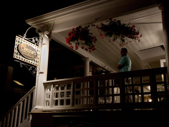 A Secret Service agent stands outside at the balcony of Chesca's Restaurant in downtown Edgartown, Mass., on Martha's Vineyard, Saturday, Aug. 20, 2016, where President Barack Obama and the first lady Michelle Obama are dining.