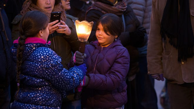Jada Degroat, 10, passes a torch to her sister, Jayanna, 7, of East Rochester before the menorah is lit in Washington Square Park in Rochester on Sunday, December 6, 2015.