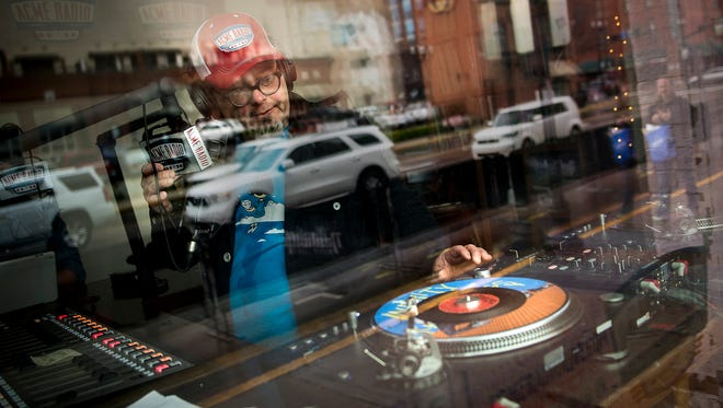 "Broadway is reflected in the window as Tim Hibbs, DJ of ""Vinyl Lunch,"" puts a record on the turntable at Acme Radio in Nashville."