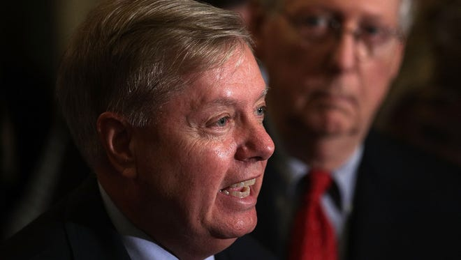 Sen. Lindsey Graham speaks as Senate Majority Leader Sen. Mitch McConnell  listens during a news briefing after the weekly Senate Republican policy luncheon at the Capitol September 19, 2017 in Washington, DC. Senate Republican held a weekly policy luncheon to discuss GOP agenda.  (Photo by Alex Wong/Getty Images) ORG XMIT: 775046359 ORIG FILE ID: 849665914
