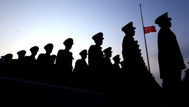 Chinese paramilitary policemen stand at attention near a Chinese flag flown at half mast to mark the 80th anniversary of the Nanjing massacre by Japanese troops in Nanjing, China. The event was held at the Nanjing Massacre Memorial Hall on Dec. 13, 2017. More than 300,000 Chinese were killed in the wartime massacre.