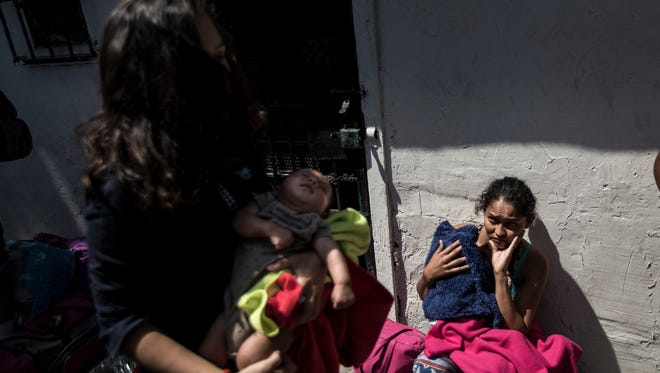 Central American mothers and children who are traveling with a caravan of migrants, wait to figure out their night's accommodations at a shelter after arriving to Tijuana, Mexico, Wednesday, April 25, 2018. The caravan of mainly Central American migrants are planning to request asylum, either in the United States or Mexico.