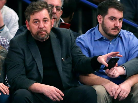 FILE - This Jan. 9, 2017 file photo shows New York Knicks owner James Dolan taking his cell phone from an assistant during the second half of an NBA basketball game between the New York Knicks and the New Orleans Pelicans at Madison Square Garden in New York. The New York Liberty are remaining under the control of Dolan and Madison Square Garden for now. The WNBA team was put up for sale in November. An MSG executive confirmed to The Associated Press on Tuesday, Feb. 6, 2018 that Dolan's group has decided to keep the Liberty at this time. (AP Photo/Kathy Willens, file)