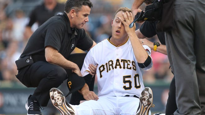 Jul 19, 2016; Pittsburgh, PA, USA; Pittsburgh Pirates starting pitcher Jameson Taillon (50) is attended to by trainer Ben Potenziano (left) after being struck with a line drive off the bat of Milwaukee Brewers third baseman Hernan Perez (not pictured) during the second inning at PNC Park.