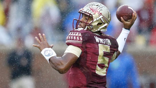 Jameis Winston throws the ball through the pouring