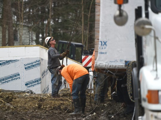 Broome-Tioga BOCES students watch as house they built for Broome County Habitat for Humanity is moved from the school property to its permanent foundation on Glenwood Road in Dickinson.