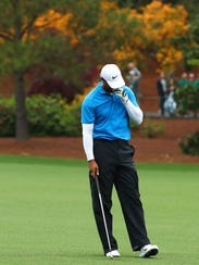 Tiger Woods reacts after hitting from the fairway on