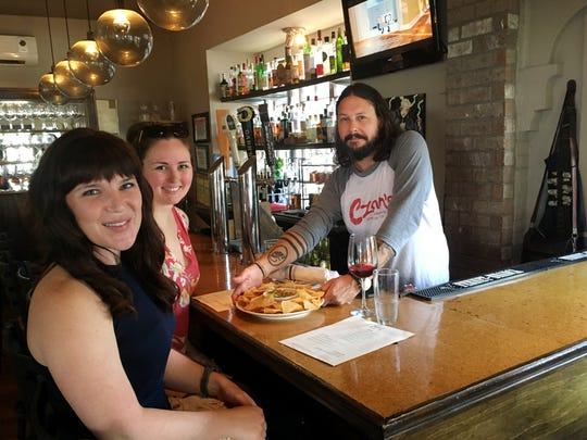 blvd bartender Brian Fill serves appetizers and wine to happy hour patrons Deanna Pouliot and Amanda Trombly.