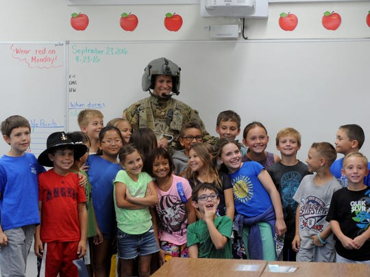 Chief Warrant Officer 2 Kyle Brantner of the California Army National Guard gets his photo taken with the third-grade class at Big Springs School in Simi Valley. Last year, when the students were in second grade, they corresponded with Brantner while he was in Iraq.