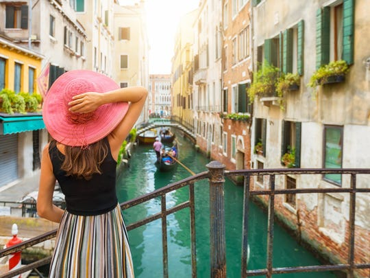 A woman in a pink hat looking out onto a Venice, Italy, canal