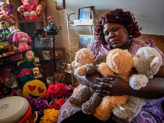 Tika Begley hugs teddy bears as she sits among her daughters collection at her new home in Nashville, Tenn., Monday, Nov. 27, 2017.