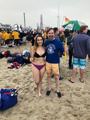 Somerset County Freeholder Brian D. Levine, with his teammate and daughter, Ariella Levine, holding their toilet plungers, the namesake for their team, as they stand on the beach in Seaside Heights.