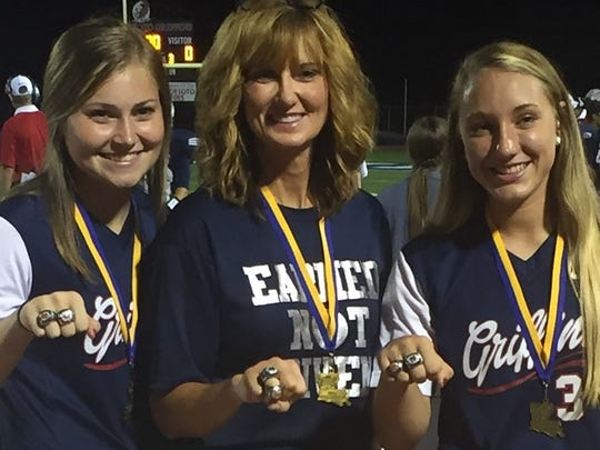 North DeSoto pitcher EC Delafield, coach Lori McFerren and shortstop Bayli Simon display their rings for winning the LHSAA Class 4A state softball title.