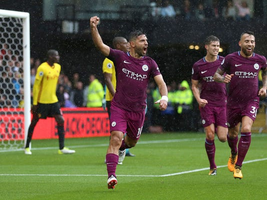 Manchester City's Sergio Aguero, centre, celebrates scoring his side's first goal against Watford during their English Premier League soccer match at Vicarage Road in Watford, England, Saturday Sept. 16, 2017. (Nigel French/PA via AP)