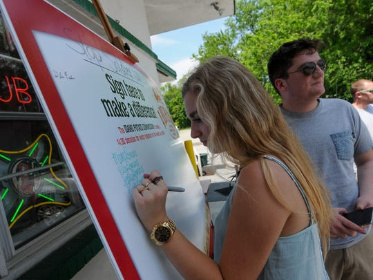 Maria Romano, 17, of Wilmington, signs her name on the board posted at the Jackson Inn in Greenville on Wednesday. If 500 signatures are reached, the Idaho Potato Growers' Association will donate $500 to 22in22, a student project aimed at preventing soldier suicide.