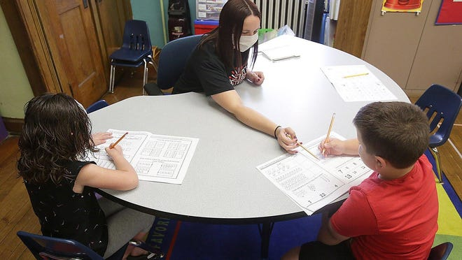 Lori Woodring, an elementary teacher, works with Amelia Zurfley, 6, and Nik Abatangelo on math skills during a federally-funded summer enrichment program at Heritage Christian School. Superintendent Sharla Elton said one month is focused on math and the next is focused on reading.