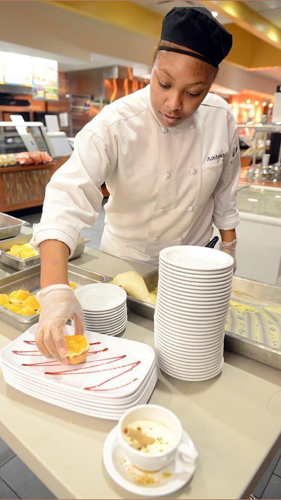 Amber Matthews, a Spencerport High School graduate, prepares dessert during a Dinner at Julia restaurant night at Finger Lakes Community College.