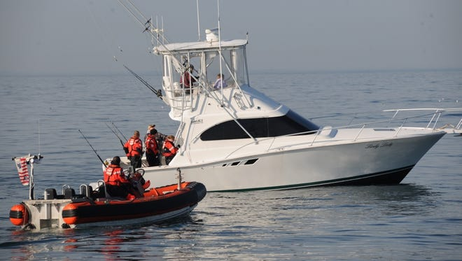 A Coast Guard boarding team from the Coast Guard Cutter Shearwater, home-ported in Portsmouth, Virginia, performs a vessel inspection aboard a recreational vessel in the waters off Virginia Beach.
