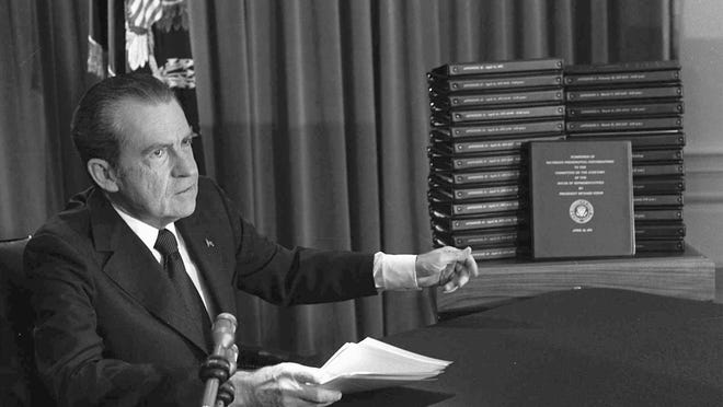 President Richard M. Nixon is shown pointing to the transcripts of the White House tapes in 1974. Nixon resigned before the House could take up impeachment.