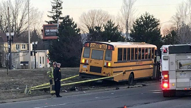 Emergency personnel stand by where a school bus jumped a curb and struck a light pole Tuesday morning, March 26, 2019, in in Lansing, Mich. Police say two students were taken to a hospital for evaluation.