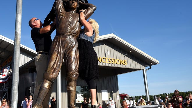 Glasgow Public Schools Superintendent Sonya Fuemmeler and former Superintendent Mike Reynolds unveil the statue of former Negro Leagues baseball star John Donaldson on Friday. The statue was unveiled at the park named after Donaldson in Glasgow, where he grew up.