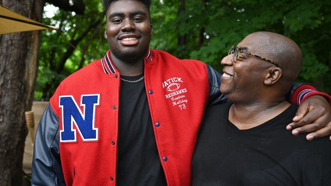 Jakobi Holiday (left) with his father, Derrick, as Jakobi played football at Natick High School.