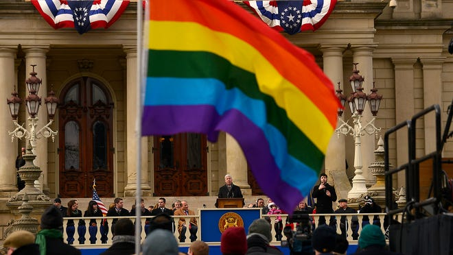 Bob Fluke of Lansing holds a rainbow flag during Gov. Rick Snyder's second inaugural ceremony on Jan. 1. In his State of the State address, the governor called for renewed discussion of protecting civil rights of LGBT citizens.