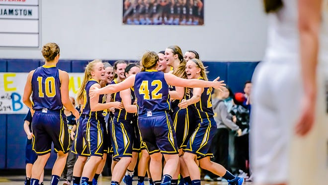 Members of the DeWitt girls basketball team celebrate after their win over Haslett on Friday.