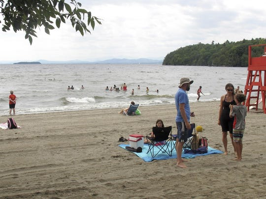 In this Aug. 14, 2015, photo, people enjoy a day along the shore of Lake Champlain at North Beach, in Burlington. The state is working to reduce the amount of phosphorous pollution that flows into the lake from Vermont.