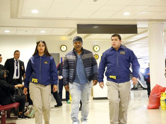 In this photo provided by the Policia de Investigacion de Chile, PDI, officers escort former heavyweight boxing champion Mike Tyson after being denied entry to the country, at the international airport in Santiago, Chile, Thursday, Nov. 9. 2017. Tyson did not meet the requirements and information needed by local laws that related to his criminal record. Tyson was jailed in 1992 for rape and went to jail in 1999 on assault charges. (Policia de Investigacion de Chile via AP)