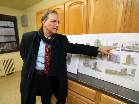 Joseph Shuldiner, the executive director of the Yonkers Municipal Housing Authority, points out some architectural drawings for updated municipal housing, while standing in a renovated kitchen at the Schlobohm Housing apartment buildings in Yonkers.