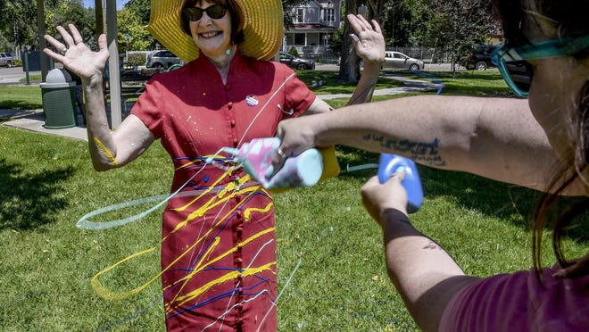 """Chris Smith, left, smiles as she holds her arms up Saturday while having her dress spatterred with paint by Hailey Knoll at A. Harold Long Park. The splatterring was part of a """"Trash the Dress"""" event by Family Crisis Services."""