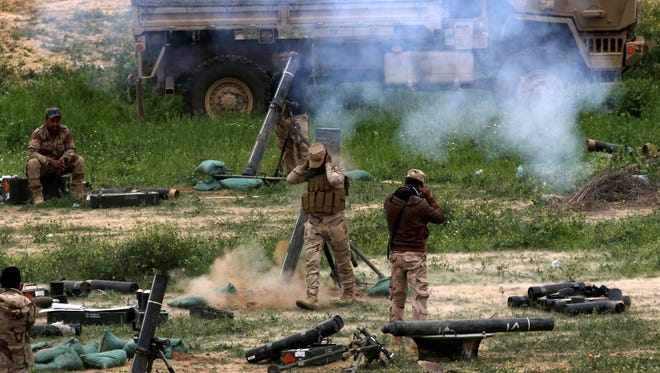 Iraqi soldiers fire mortar shells as they hold a position on the outskirts of Makhmur, north of the capital Baghdad, March 26, 2016.