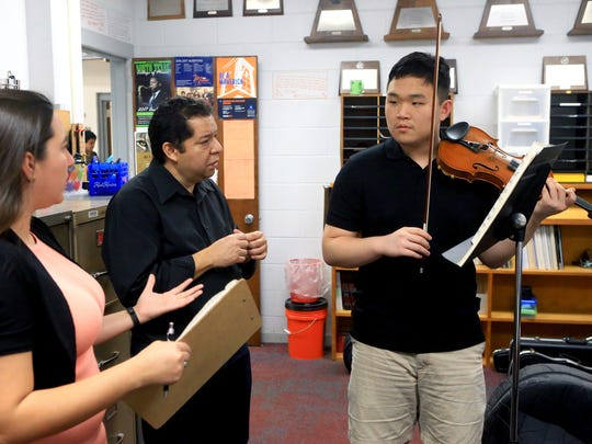 Alex Jeoung (right) gets help from orchestra director April Ibarra (left) and private instructor Dr. Jose Flores, from Texas A&M University-Corpus Christi, during practice Tuesday, Jan. 24, 2017, at Ray High School in Corpus Christi.