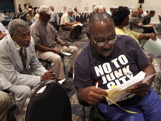 """Willie Green, right, President of the Justice For All People Foundation, wears a """"No to Junk City"""" t-shirt to a Fort Myers City Council meeting concerning the Garden St. Iron & Metal, Inc. junkyard expansion project Monday."""