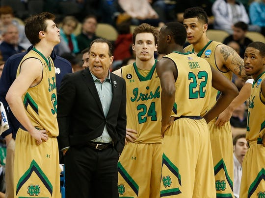 Notre Dame Fighting Irish head coach Mike Brey (L) huddles with his team during a stoppage in play against the Butler Bulldogs in the third round of the 2015 NCAA Tournamentat Consol Energy Center.