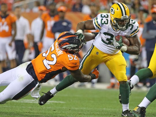 Green Bay Packers running back Aaron Jones runs past the tackle of inside linebacker Corey Nelson during a 2017 preseason game against the Denver Broncos at Sports Authority Field at Mile High. The Packers host the Broncos at Lambeau Field on Sunday.