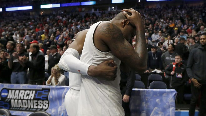 Cincinnati Bearcats senior forward Gary Clark is consoled by a teammate after Sunday's 75-73 loss to Nevada, in an NCAA Tournament second-round game in Nashville.