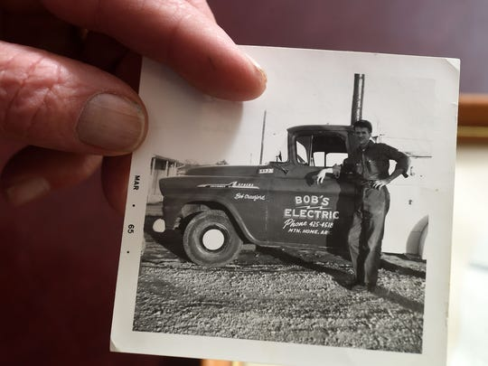 Bob Crawford holds a photograph made in 1965, his first year in business. The company's first phone number, shown on that first truck, is still in use.