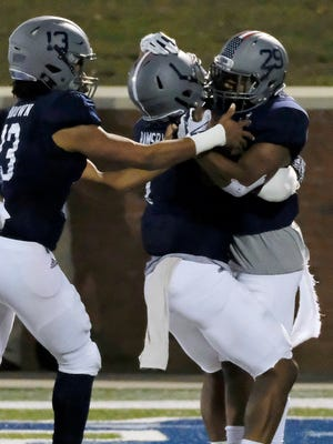 Georgia Southern running back Demarcus Godfrey is congratulated by teammates LA Ramsby and Kado Brown (left) after scoring a touchdown against South Alabama last season.