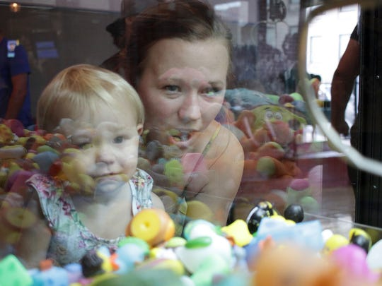 Krissy Weber tries to win a duck with the claw machine game for 2-year-old Luna at Filly's restaurant in Gallaitn, TN on Thursday, June 21, 2018.