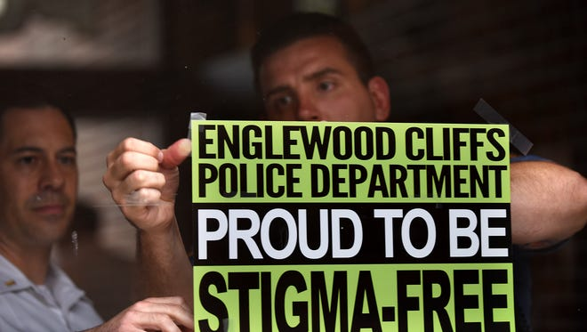 """Englewood Cliffs Police Department goes stigma free. Lt. William Henkelman and Daniel O'Shea put up a """"Stigma-Free"""" sign on the door to the Englewood Cliffs Police Department on Tuesday July 03, 2018."""