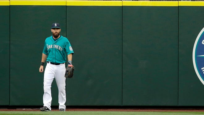 Los Angeles Angels fans in the outfield seats cheer as Seattle Mariners center fielder Dustin Ackley walks away from the wall after being unable to stop a three-run home run by Angels' Mike Trout during the third inning of a baseball game, Friday, July 10, 2015, in Seattle.