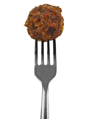 Freshly cooked meatball on a silver fork.